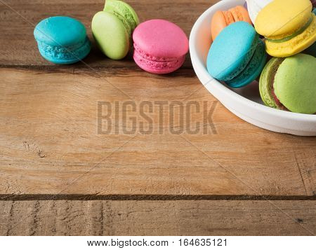 Sweet and colourful french macaroons or macarons in container ceramic white was placed wooden table. Background of dessert for St Valentine's Day. Selective and soft focus. Vintage Pastel