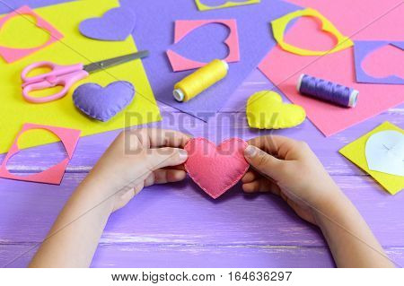 Small child holds a pink felt heart in his hands. Child shows heart crafts. Craft tools and materials on a wooden table. Valentine's day or mother's day handmade gifts. Art of hand sewing