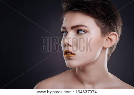 Who is here. Pleasant concentrated woman looking aside and posing against black background
