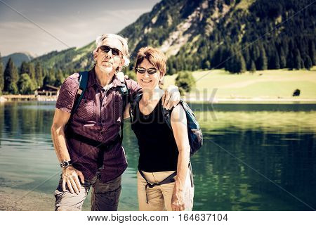 A senior couple is taking a break by the lakeside.