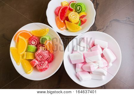 Multicolored fruit candy and marshmallow in a white bowl. Delicious and beautiful dessert.