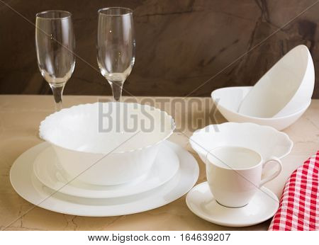 Various white dishware on a marble background