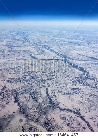 Aerial view taken on flight over the vast expanse of frozen rivers and snow landscape of Northern Canada