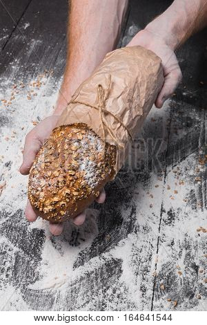 Warm fresh rye whole grain bread, wrapped in craft paper. Healthy baking and cooking concept background. Hands carefully hold loaf on wooden table background, sprinkled with flour. Soft toning