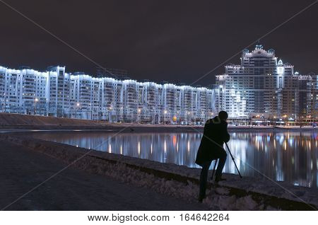 Man shooting reflections in river. Silhouette of man photographer with digital camera and tripod taking picture of night view of city in winter.
