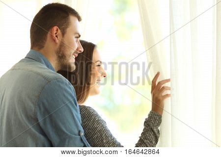 Affectionate marriage opening curtains and looking outside through a window in a new beautiful day with a warm light