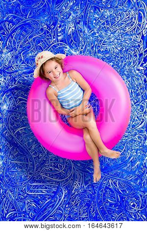 Happy little 5 year old girl enjoying her summer vacation floating in the swimming pool on a bright pink tube and grinning at the camera conceptual image on blue painted water background with ripples