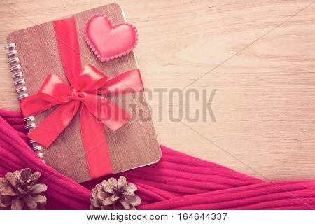 notebook wrapped with red ribbon red felt hearts in vintage pink color tone all on wooden table good for valentine or special occasion