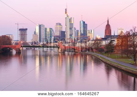 Picturesque view of business district with skyscrapers and mirror reflections in the river at sunrise, Frankfurt am Main, Germany