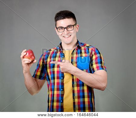Man With Apple Isolated On Gray Background
