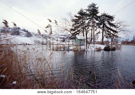 Snowed landscape and cabane on island in lake saint andre savoy france