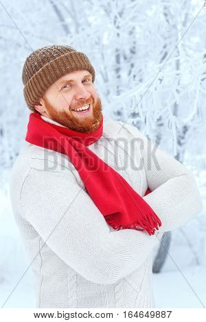 young redhead man with beard in hat and scarf outdoors in winter forest. Portrait of the ginger bearded man. Happy man with stylish red beard and mustache is laughing at winter park background