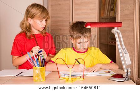 Education childhood people homework and school concept - children writing in notebooks at home