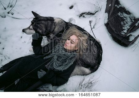 Girl with big malamute dog on winter background. She lies near dog and put her head on dog's back.