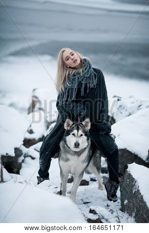 Girl with dog Malamute among rocks in winter. She sits astride dog among rocks.