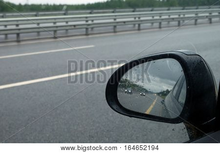 Riding cars reflected in car side mirror on suburban highway in rainy weather