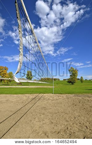 An outdoor volleyball net stretches across a sand court