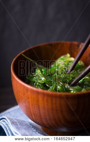 Chuka salad in the wooden bowl on the dark background