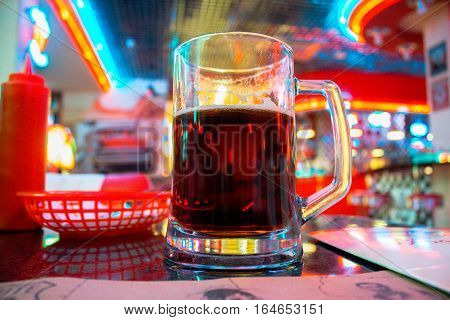 Dark beer in a mug on a table in a bar