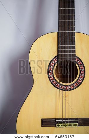 Guitar on wooden background fretboard, stringed musical instrument