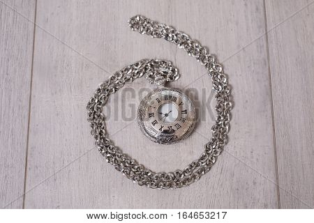 closed pocket watch lying on a light wooden background