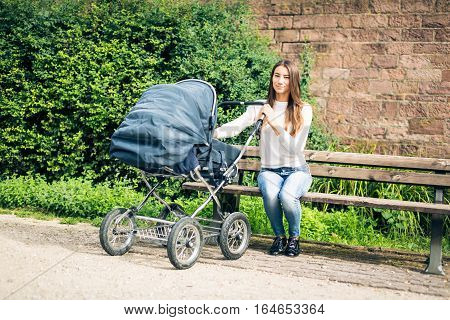 Young mother enjoying time outdoors, taking the baby to a park along the banks of the river Neckar in Heidelberg, Germany.