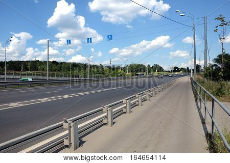Cityscape with urban highway and pedestrian way with fence in sunny summer day horizontal photo side view closeup