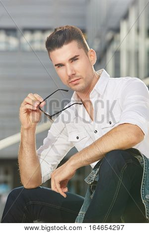 Attractive Man Staring Sitting Outside In City