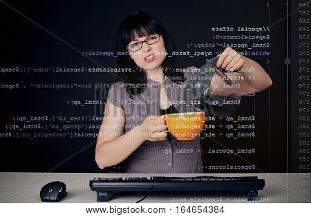 young woman with glasses sitting in front of a computer, programming. the code she is working on php can be seen through the screen.