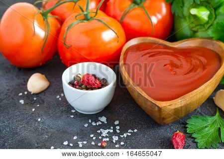 Wooden bowl with tomato ketchup and ingredients selective focus