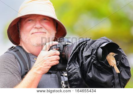 Santiago Island, Ecuador -april 22: Galapagos Flycatcher Sits On Lens Hood Of Man (blurred) On Santi