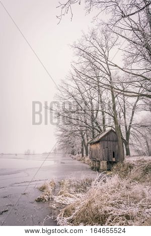 Lonely Wooden Hut Next To Frozen Pond In Foggy Day