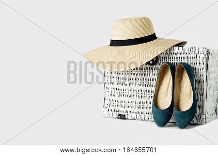 White wicker suitcase a woman's hat and blue shoes.