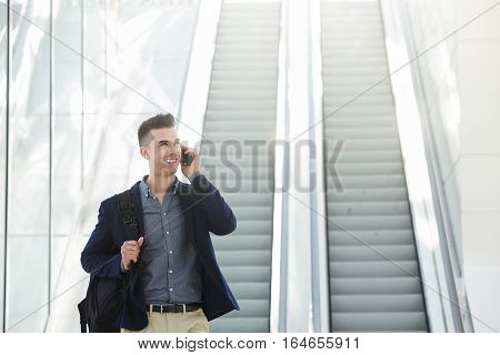 Portrait of handsome business man by escalator on phone call