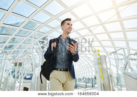 Smiling Business Man By Airport Turnstile With Cellphone