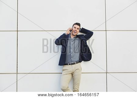 Laughing Business Man On Mobile Phone With Hand Behind Head