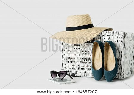 White wicker suitcase womens hat sunglasses blue shoes and e-book.