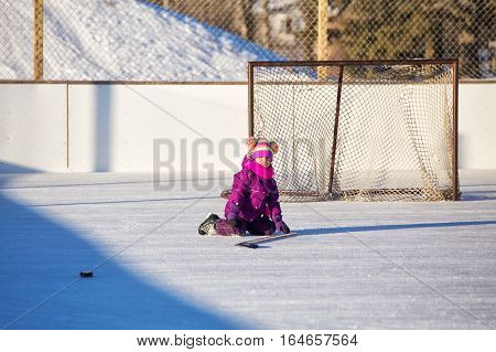 Four year old girl wearing pink and purple jacket and ski pants and hockey skates sitting on an outdoor ice skating rink in front of a net in winter