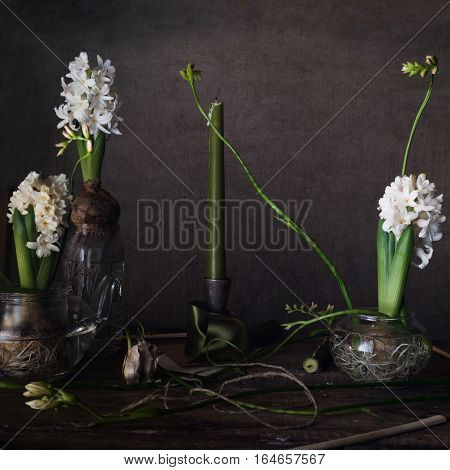 three white hyacinth and freesia in transparent vases, candle on a dark background.