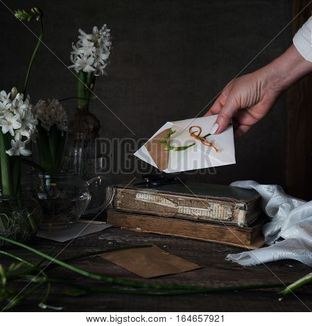female hand holding out a letter with the envelope on a dark background.