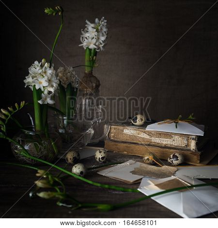 Still life with old books, quail eggs, white hyacinths on a dark background