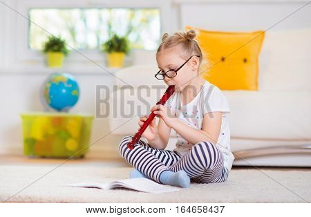 Portrait Of Pretty Little Girl With Flute On Floor