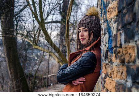 Portrait of a beautiful stylish fashionable woman on the background of the city painted wall with bricks and in leather jacket and hat with fur