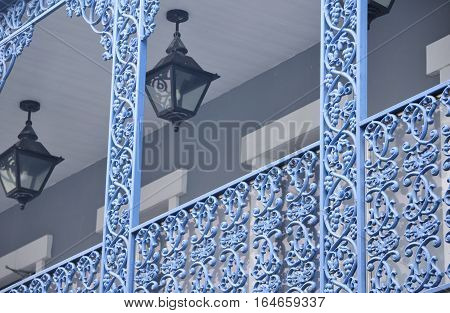 An intricately designed blue painted metal railing on a balcony of a building in the city of macau china at Fisherman's wharf.