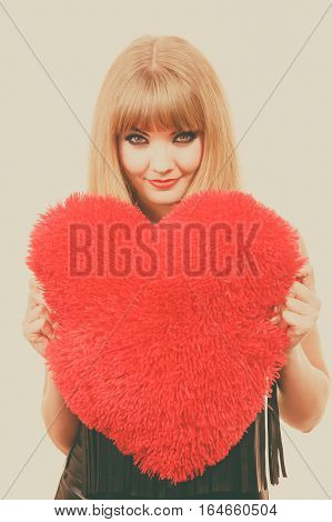 Woman elegant blonde long hair girl dark makeup red lipstick holding red heart love symbol flirting studio shot toned image. Valentines day happiness concept