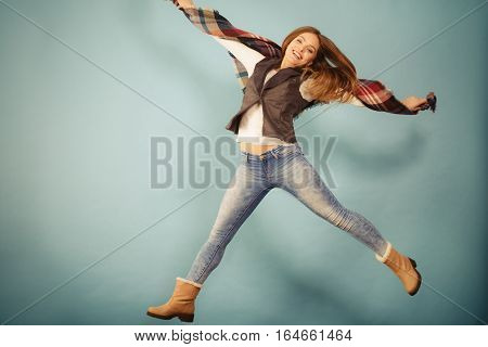 Fun and fashion concept. Woman fashionable casual style autumn girl jumping flying in air on blue