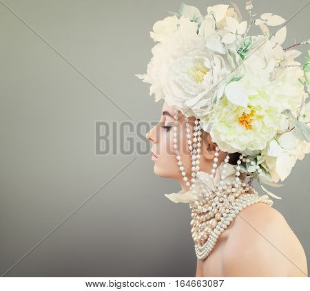 Summer Beauty. Beautiful Model Woman with Flowers and Jewelry on Background with Copyspace