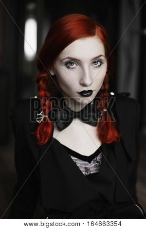 Portrait of red-haired girl in bow tie on a dark background gothic style girl with pigtails a girl in a black dress fashion style girl in dress and in a black cloak coat black lips sitting