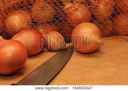 Onions perforated bag and a knife on a wooden plank