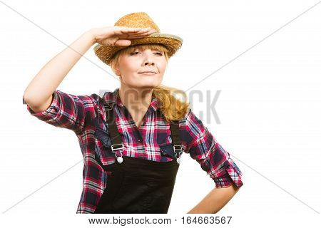Gardening concept. Attractive woman in dungarees pink check shirt and sun hat looking into the distance. Isolated background